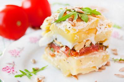 Zapiekanka z ziemniaków, pomidorów, jajek i rukoli posypana ...