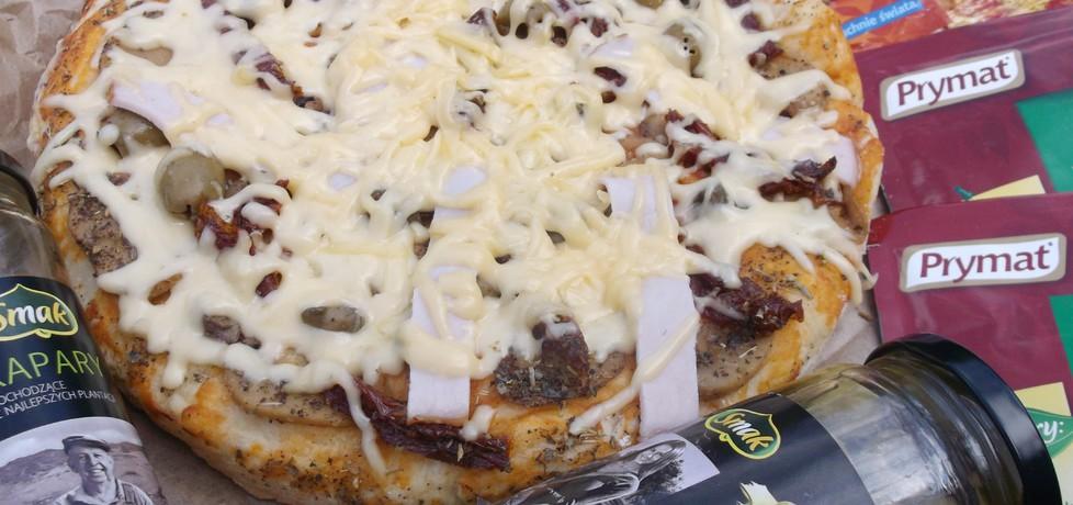 Pizza z suszonymi pomidorami,kaparami i oliwkami. (autor ...